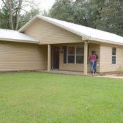 Two people in front of Habitat Chipola's new home
