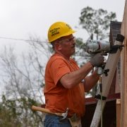 Man Attaches Plywood with Nailgun
