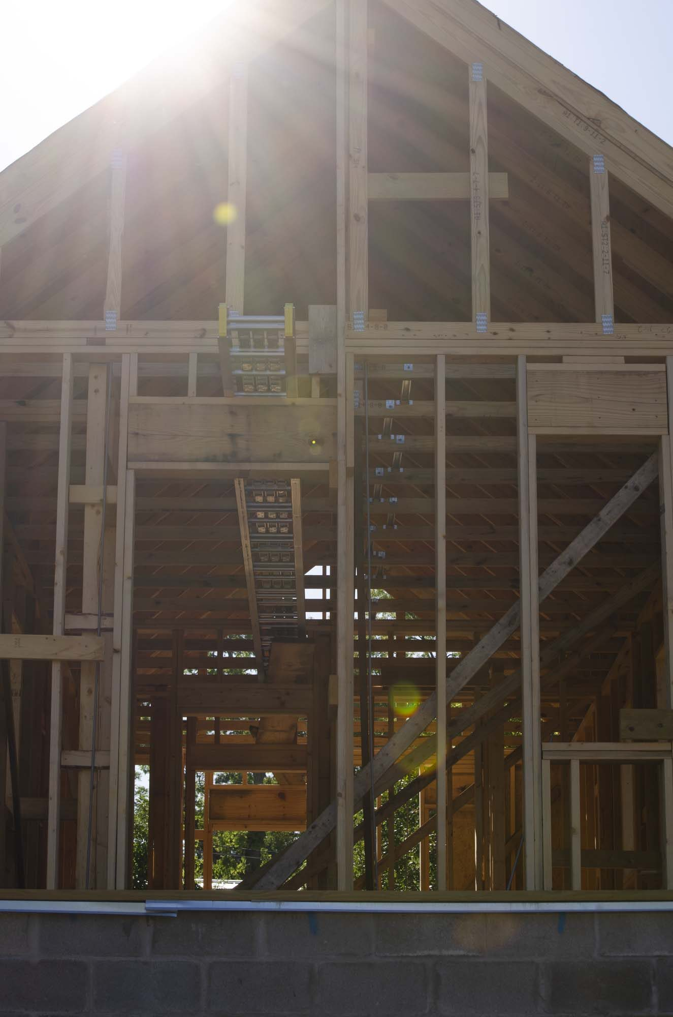 A photograph of a home under construction in Marianna, Florida. The image shows the sun streaming over the roofline of the wood frame and block foundation of an unfinished home. The Dream Builders monthly giving program provides a foundation for building homes like this for families in need.